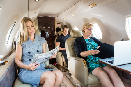 Business people traveling in corporate jet photo