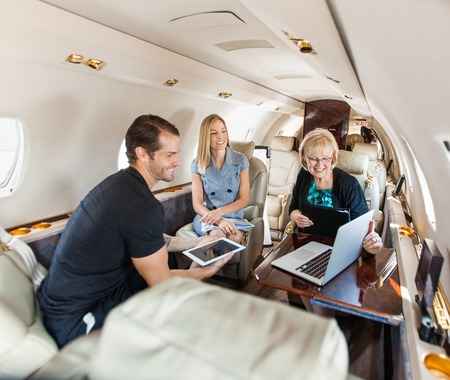 Mensen uit het bedrijfsleven die discussie over laptop op prive-jet