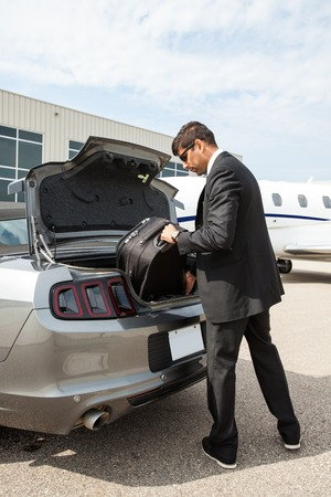 unloading: Full length of businessman unloading luggage from car boot at airport terminal Stock Photo