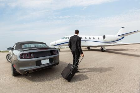 Biznesmen z bagażem samochodem i stoi prywatny odrzutowiec na terminal lotniska