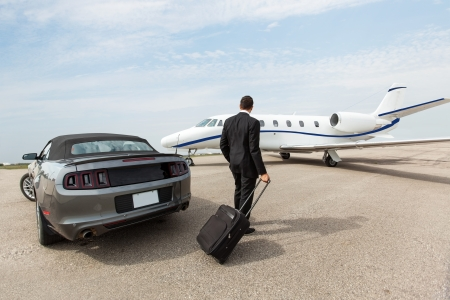 Businessman with luggage standing by car and private jet at airport terminal