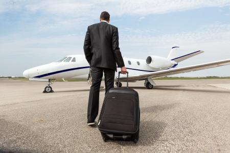 企業専用ジェット機に向かって歩いて荷物を持ったビジネスマンの背面図