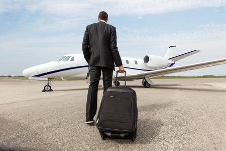 Rear view of businessman with luggage walking towards corporate jet photo