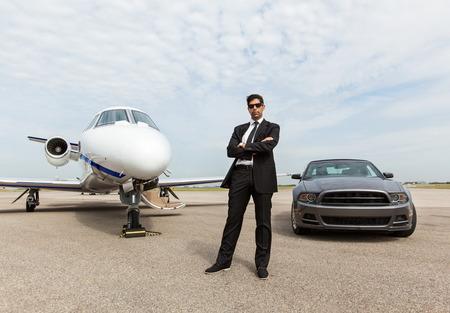 Volledige lengte van zelfverzekerde zakenman staat met de auto en prive-jet op de luchthaven terminal
