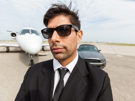 Portrait of confident mid adult businessman in front of car and private jet at terminal photo