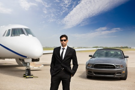 wealthy: Portrait of confident male entrepreneur standing in front of car and private jet at terminal Stock Photo