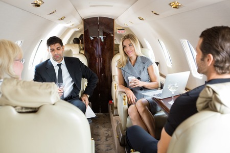 Businesswoman with colleagues having drinks on private jet photo