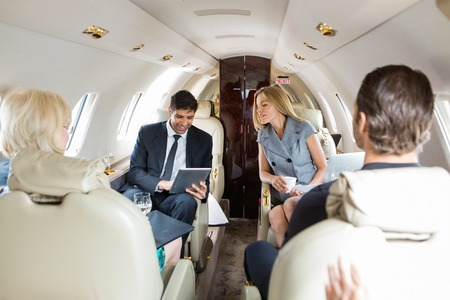 private: Businessman using digital tablet with colleagues in private jet