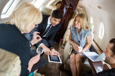 Businessman showing project on digital tablet with colleagues in private jet