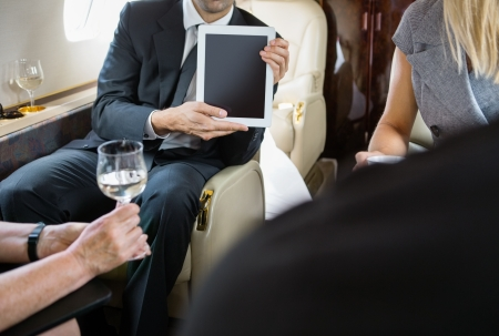 private jet: Cropped image of businessman showing digital tablet to colleagues in private jet