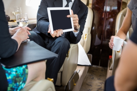 Businessman showing project on digital tablet to partners in private jet photo