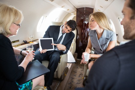 small plane: Businessman showing project on digital tablet to partners in private plane