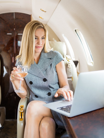 first plane: Beautiful businesswoman holding wineglass while using laptop in private jet