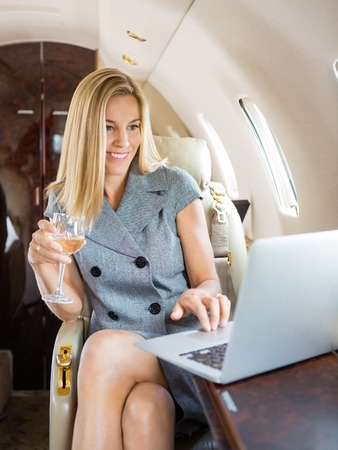airplane: Happy businesswoman holding wineglass while using laptop in private jet