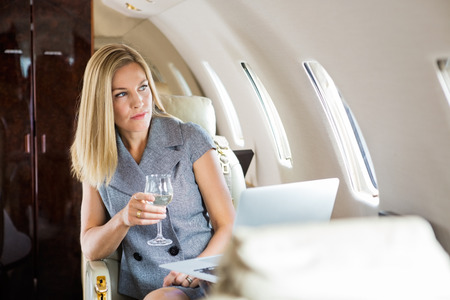 Beautiful businesswoman holding wineglass while looking through window of private jet