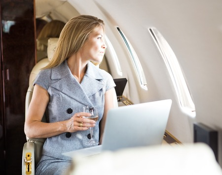 first plane: Mid adult businesswoman holding wineglass while looking through window of private jet
