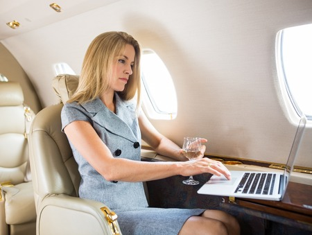 first plane: Confident businesswoman with wineglass using laptop in private jet