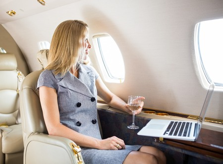 private jet: Happy businesswoman holding wineglass while looking through window of private jet