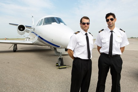 airline pilot: Portrait of confident pilots standing in front of private jet Stock Photo