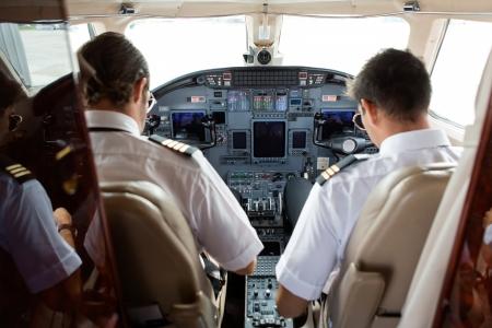プライベート ジェットのコックピットで操縦者そしての背面図
