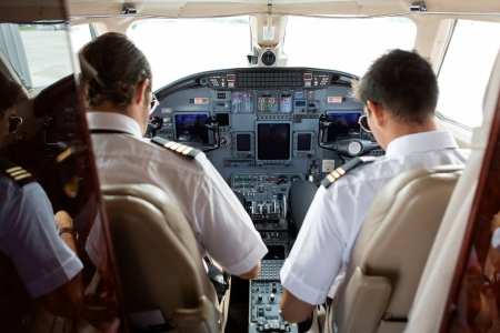 corporate jet: Rear view of pilot and copilot in cockpit of private jet