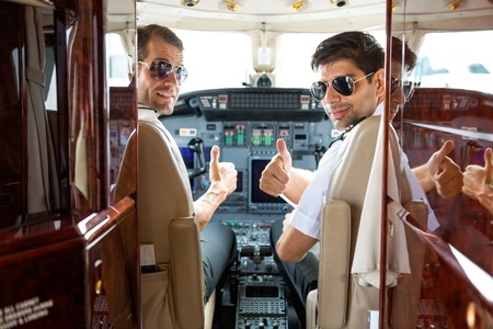 Portrait of confident pilots gesturing thumbs up in cockpit of private jet photo