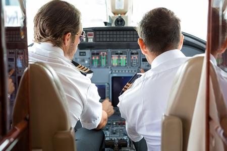 pilot cockpit: Rear view of pilot and copilot in private jet cockpit