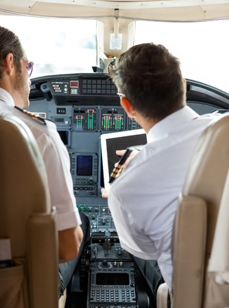 piloto: Vista trasera del piloto y el copiloto que usa la tableta digital en cabina del jet privado
