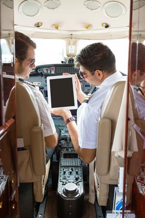 ビジネス ジェットのコックピットの副操縦士にデジタル タブレットを示すパイロット