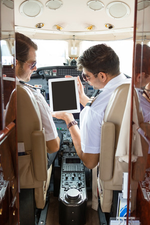 Pilot showing digital tablet to copilot in cockpit of corporate jet Фото со стока