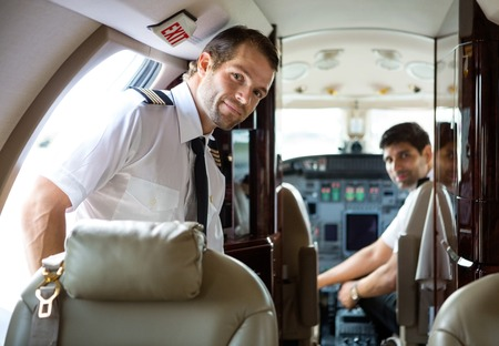 corporate jet: Portrait of handsome pilot entering private jet with copilot in background Stock Photo