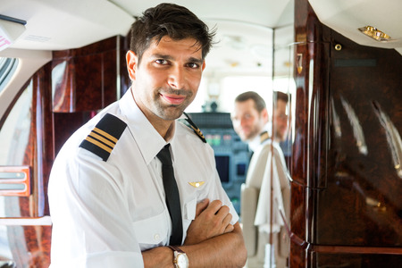 Portrait of confident pilot with copilot in background of private jet photo