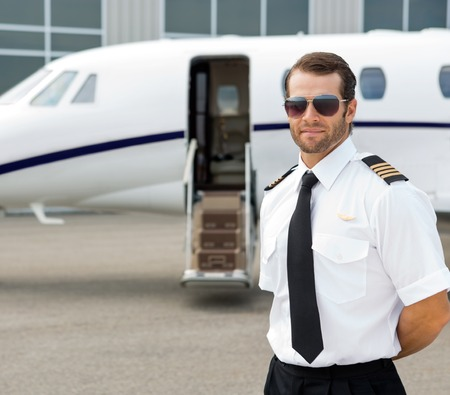 airline pilot: Portrait of confident pilot wearing sunglasses with private jet in background