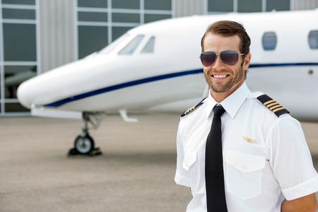 piloto de avion: Piloto confidente que sonr�e delante de jet privado
