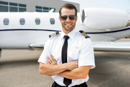 private jet: Portrait of confident pilot smiling in front of private jet Stock Photo