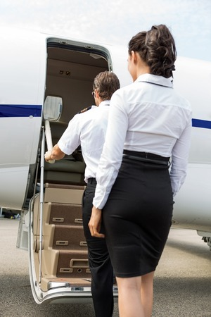 Rear view of stewardess and pilot boarding private jet