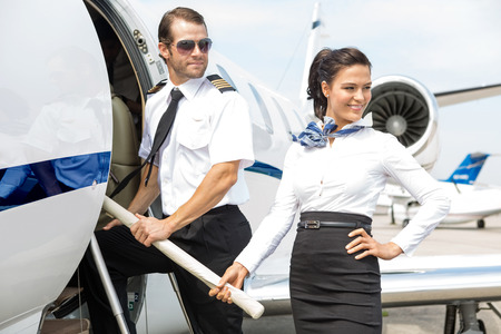 an attendant: Beautiful airhostess with pilot boarding private jet