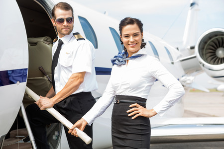Portrait de la belle hôtesse de l'air avec le pilote d'embarquement jet privé