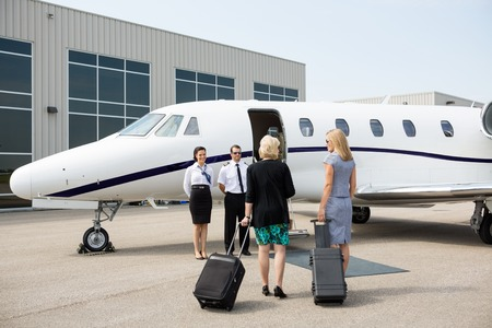 Rear view of businesswomen with luggage walking towards private jet while pilot and airhostess standing by photo