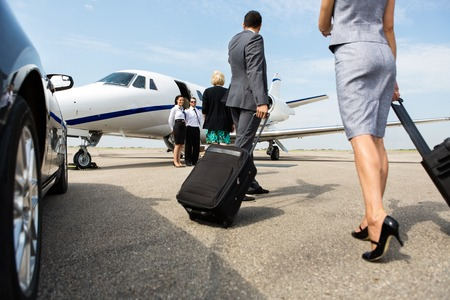 Business partners with luggage walking towards private jet at terminal