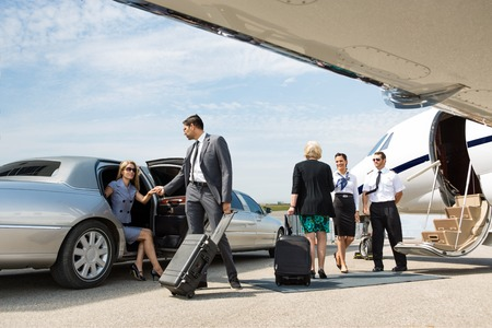Bedrijfspartners aan boord prive-jet, terwijl stewardess en piloot te begroeten