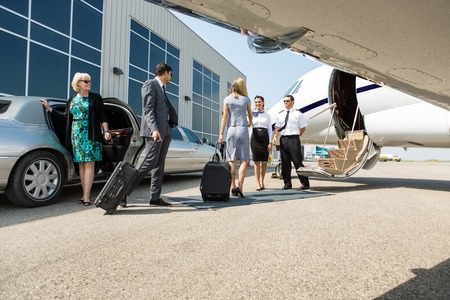 Airhostess and pilot greeting business people before boarding private jet photo