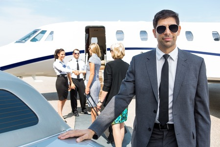 Portrait of confident businessman with airhostess and pilot greeting businesswomen against private jet photo