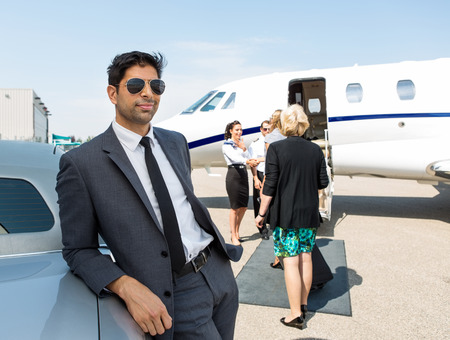 Confident businessman leaning on car with airhostess and pilot greeting business people against private jet photo