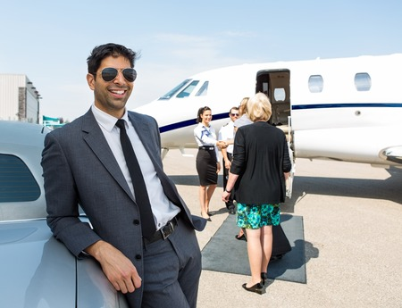Happy businessman leaning on car with airhostess and pilot greeting business people against private jet photo