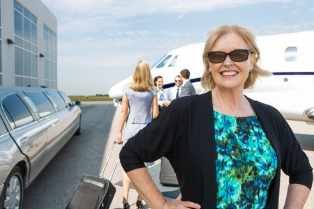 Portrait of happy mature businesswoman with limousine and private jet in background photo