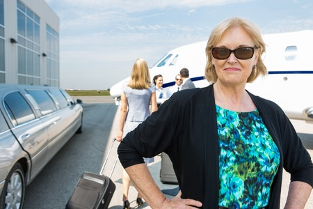 Portrait of confident mature businesswoman with limousine and private jet in background photo