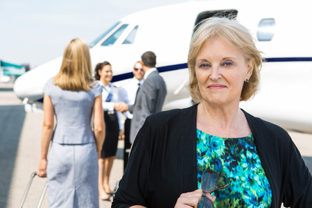 Portrait of confident businesswoman with airhostess greeting business people near private jet photo