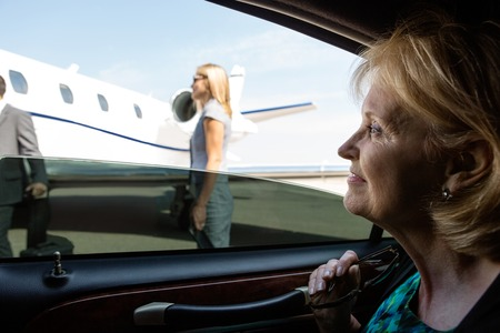 Thoughtful mature businesswoman in car looking at private jet photo