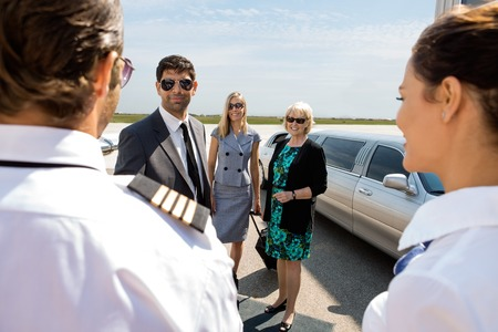 Confident businessman with colleagues greeting pilot and airhostess at airport terminal photo